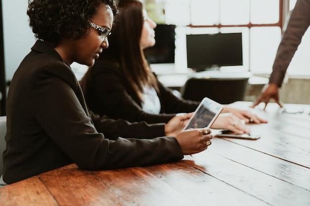 Femme d'affaires noire lors d'une réunion à l'aide d'une tablette numérique