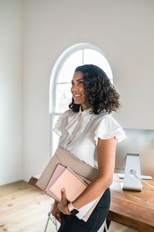 Femme d'affaires noire portant un appareil numérique