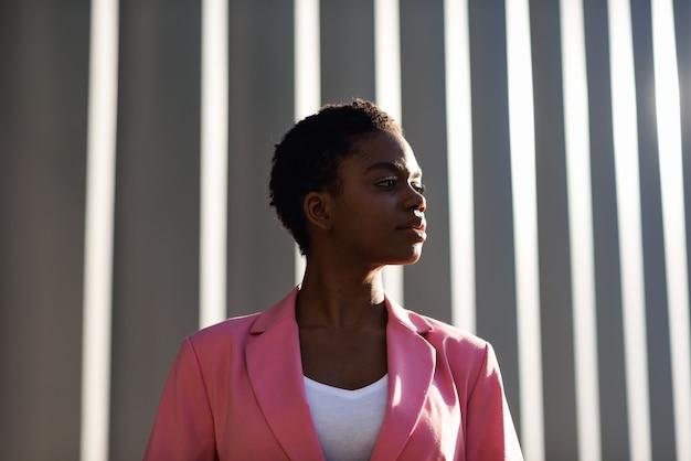 Femme d'affaires noire souriante debout près d'un immeuble de bureaux