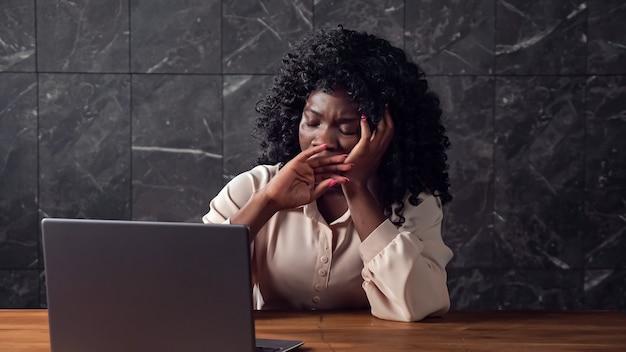 Femme d'affaires noire avec des types de cheveux bouclés sur un ordinateur portable paresseusement