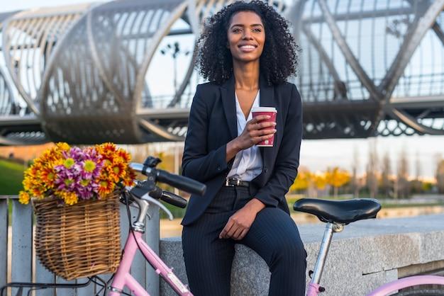 Femme d'affaires noire avec vélo vintage boire du café