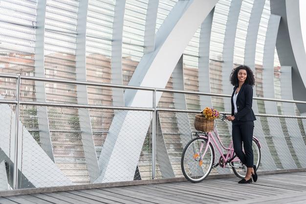 Femme d'affaires noire avec vélo vintage dans un pont