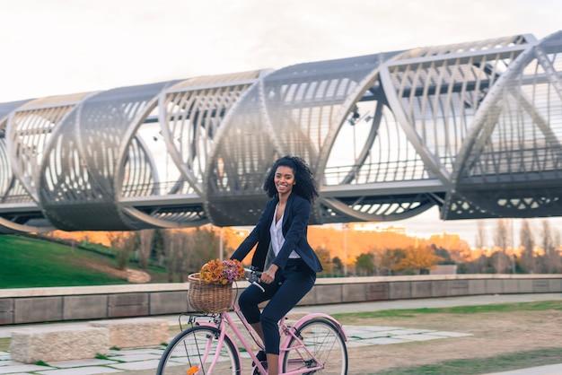 Femme d'affaires noire sur un vélo vintage dans la ville