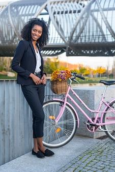 Femme d'affaires noire avec vélo vintage