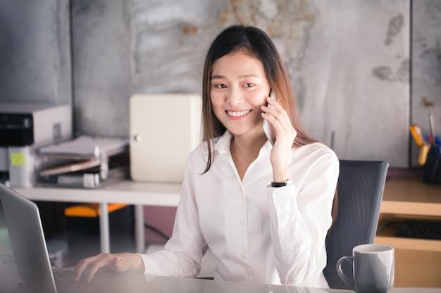 Femme d'affaires de nouvelle génération à l'aide de smartphone, femme asiatique travaillent heureusement au bureau