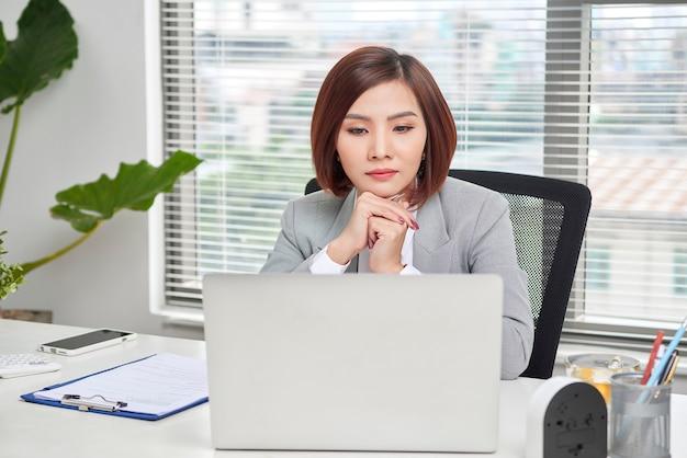 Femme d'affaires occasionnelle réfléchissant à la possibilité de rechercher de nouvelles opportunités commerciales. design minimaliste. table en bois. lieu de travail confortable avec un ordinateur portable
