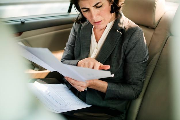 Femme d'affaires occupé à l'intérieur de la voiture