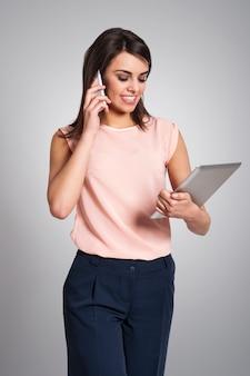 Femme d'affaires occupée avec équipement électronique