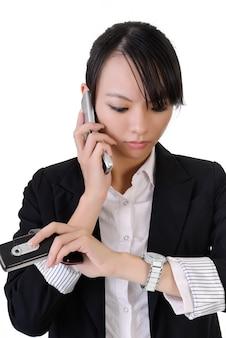 Femme d'affaires occupée tenant des téléphones portables et regarder la montre, portrait agrandi sur fond blanc.