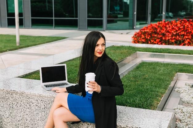 Femme d'affaires avec ordinateur portable et coupe d'élimination assis à l'extérieur de l'immeuble de bureaux