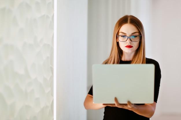 Femme affaires, à, ordinateur portable, dans, robe noire, dans, bureau blanc