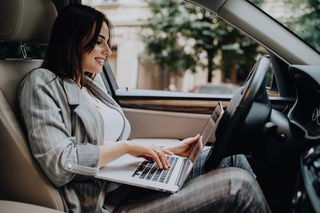 Femme d'affaires avec un ordinateur portable dans sa voiture dans la rue