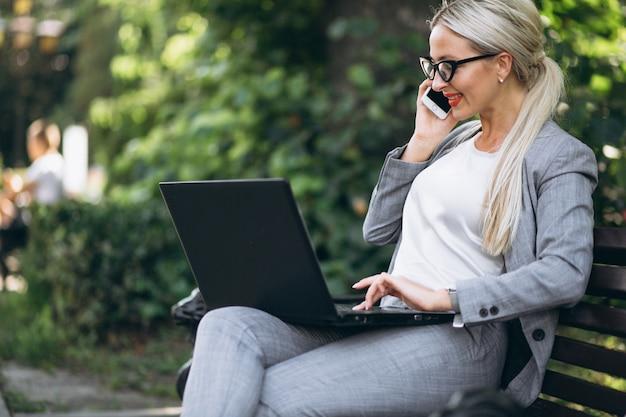 Femme d'affaires avec un ordinateur portable parlant au téléphone dans un parc sur un banc