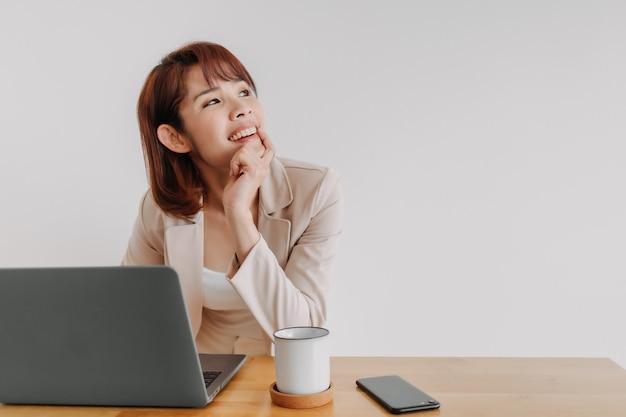 Femme d'affaires avec ordinateur portable regarde l'espace vide