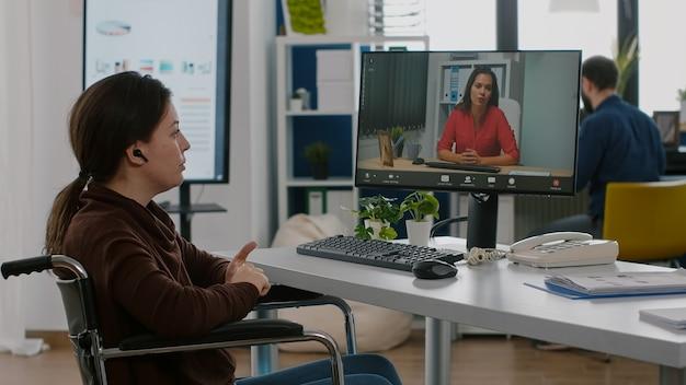 Femme d'affaires paralysée handicapée invalide parlant en vidéoconférence