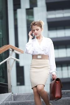 Femme d'affaires parlant au mobile en milieu urbain
