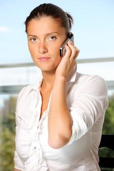 Femme d'affaires parlant au téléphone sur le beau fond extérieur