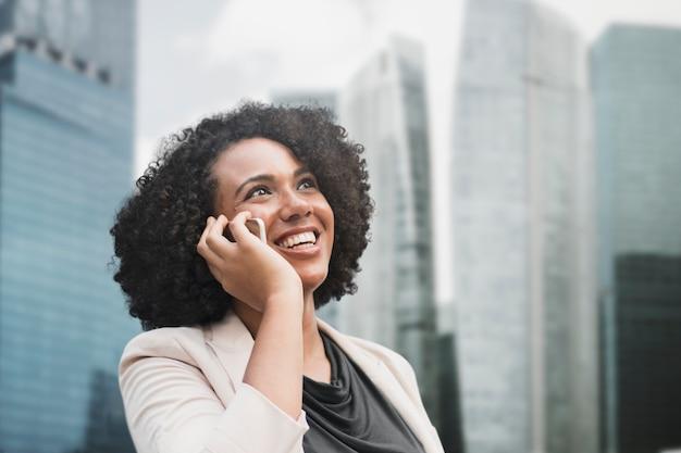Femme d'affaires parlant au téléphone dans les médias remixés de la ville