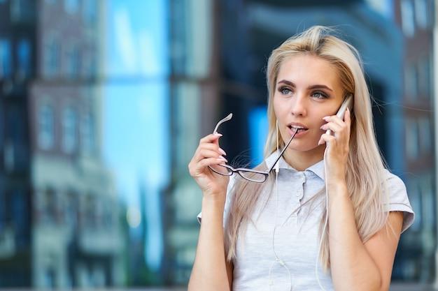 Femme d'affaires parlant au téléphone, tenant des lunettes