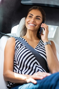 Femme d'affaires parlant. femme d'affaires occupée parlant par téléphone avec un partenaire commercial assis dans la voiture