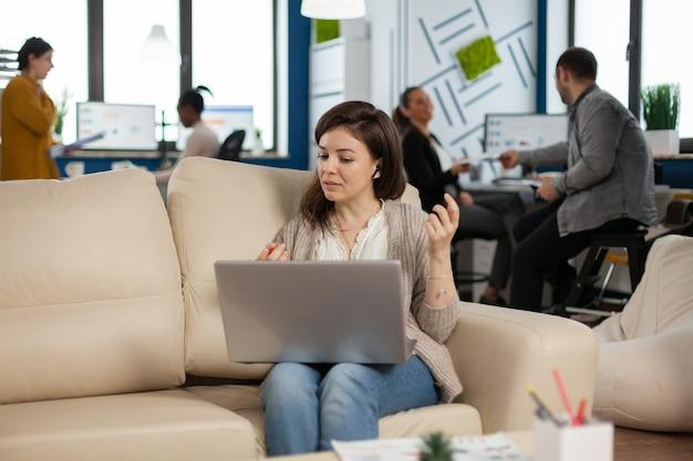 Femme d'affaires parlant lors d'appels de vidéoconférence depuis un ordinateur portable assis sur un canapé