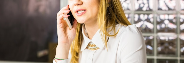 Femme d'affaires parlant sur son téléphone portable au bureau