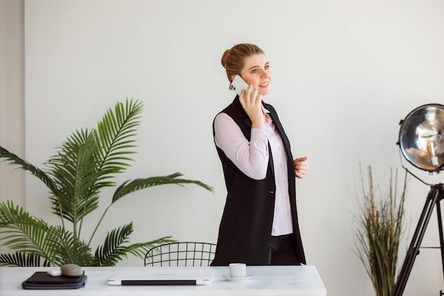 La femme d'affaires parle au téléphone dans le bureau moderne blanc