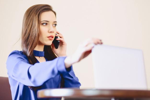 Femme d'affaires parle par téléphone au bureau et travaille sur un ordinateur portable