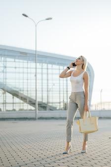 Femme affaires, parle téléphone, quoique, debout, dans, extérieur