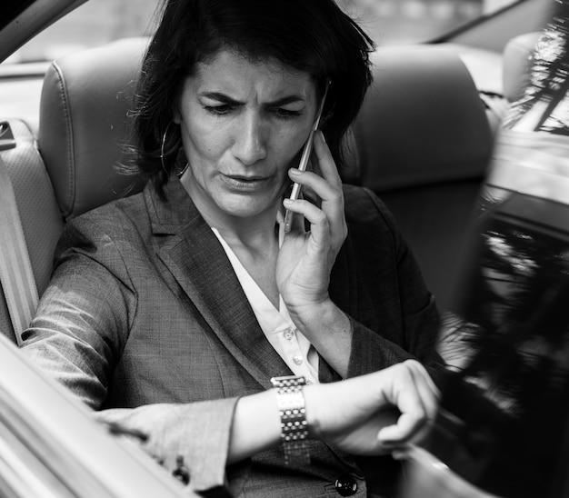 Femme d'affaires, parler à l'aide de voiture de téléphone à l'intérieur