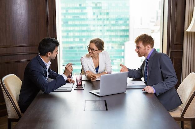 Femme d'affaires de parler avec deux hommes d'affaires