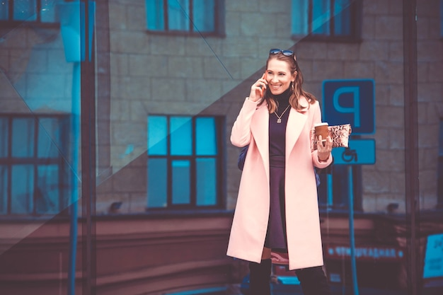 Femme d'affaires sur une pause-café à l'heure du déjeuner. elle parle au téléphone et rit. dans son autre main tient une tasse de café en papier à emporter.