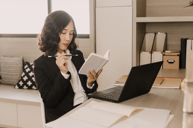 Femme d'affaires pense écrire quelque chose sur le cahier.