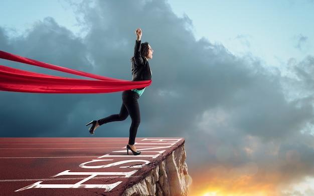 Une femme d'affaires pense qu'elle a gagné mais il y a un précipe après la ligne d'arrivée