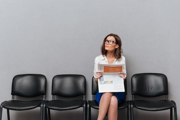 Femme d'affaires pensif à lunettes assis sur des chaises