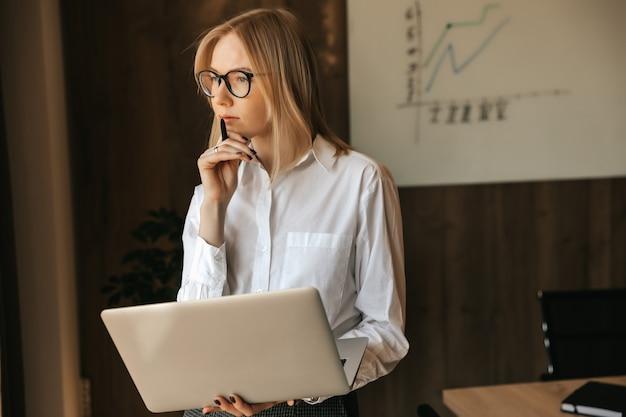 Femme d'affaires pensive travaillant sur un ordinateur portable, pensant à une tâche lourde, travail de bureau.