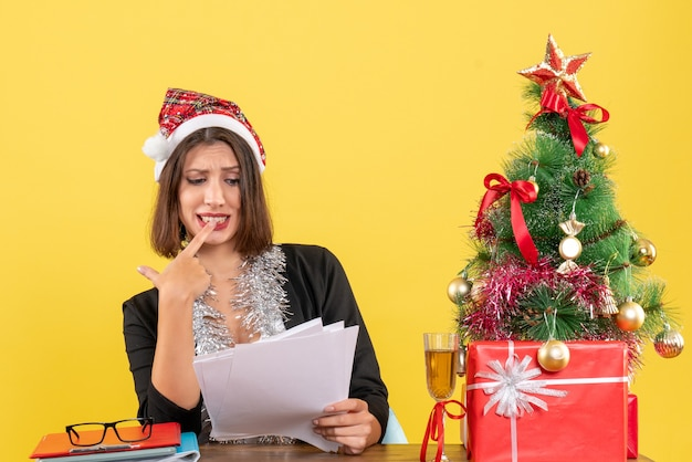 Femme d'affaires perplexe en costume avec chapeau de père noël et décorations de nouvel an tenant des documets et assis à une table avec un arbre de noël dessus dans le bureau