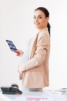 Femme d'affaires avec photo sonogramme. femme d'affaires enceinte joyeuse tenant une image radiographique d'un bébé et souriant tout en se tenant près de son lieu de travail