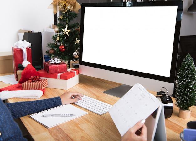 Femme d'affaires avec planificateur de calendrier et écran d'ordinateur en vacances de noël