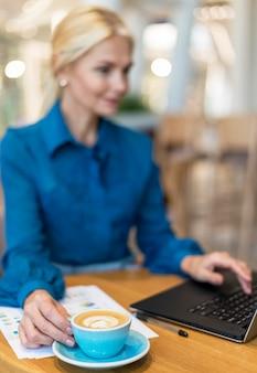 Femme d'affaires plus âgée défocalisée travaillant sur ordinateur portable et prendre un café