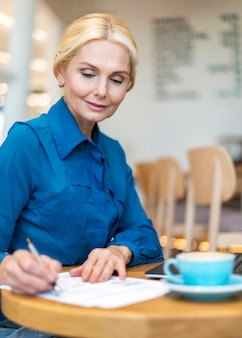 Femme d'affaires plus âgée travaillant sur des papiers tout en prenant un café