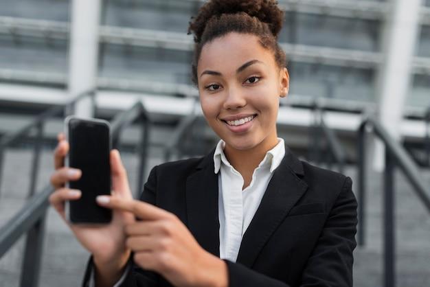 Femme d'affaires pointant au téléphone