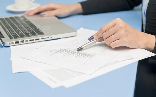 Femme d'affaires pointant un projet d'entreprise et d'analyser les informations de données de marché, concept de travail