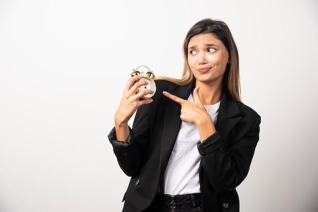 Femme d'affaires pointant sur un réveil sur un mur blanc.