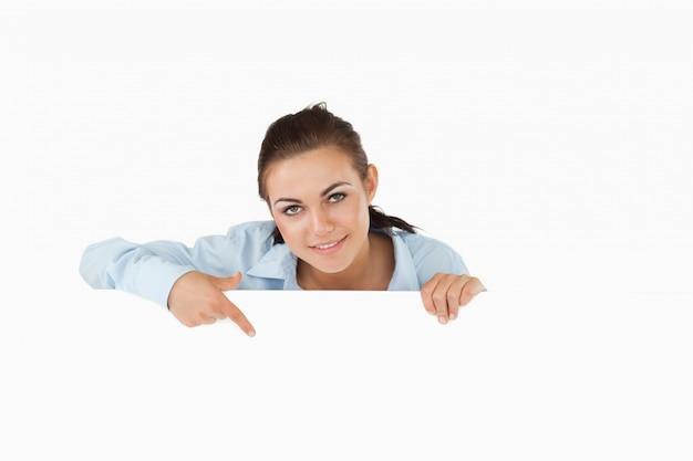 Femme d'affaires pointant sur signe sous elle