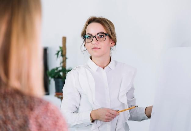 Femme d'affaires pointant sur un tableau blanc tout en présentant ses idées à des partenaires commerciaux