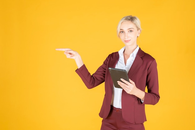 Femme d'affaires pointe quelque chose sur fond jaune
