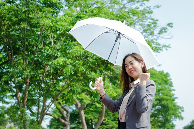 Une femme d'affaires portant un costume, elle tient un parapluie blanc ombragé. et leva une main heureuse pour travailler avec succès