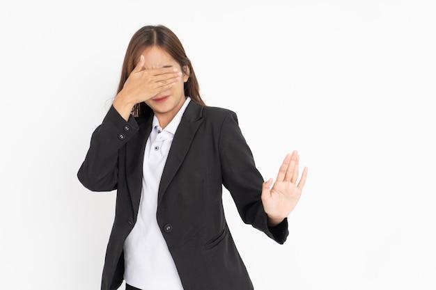 Femme d'affaires portant un costume noir fermant les yeux avec un geste de la main de rejet