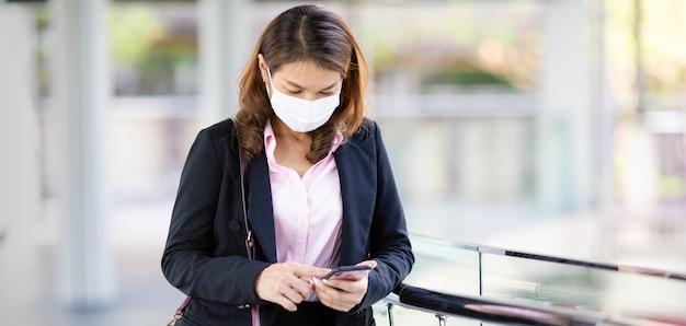 Femme d'affaires portant un masque parler téléphone.